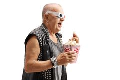 Old punker wearing a pair of 3D glasses eating popcorn and laugh. Ing isolated on white background stock photo
