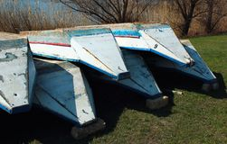 Old punt boats lay upside down on a shore.  Stock Photo