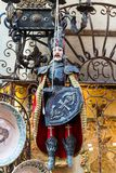 Old puppet or marionette of a knight in amour. With a shield and red cloak hanging in an antique store Royalty Free Stock Image