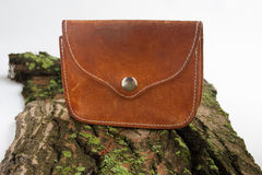 Old purse made of genuine leather on a background of old wood. Purse in country style Stock Images