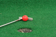 Old Putter. And golf ball at worn-out miniature golf course. Concept photo Royalty Free Stock Image