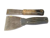 Construction tools. Closeup of old used putty knives on white background Stock Images