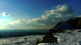 Old quarry covered in snow. With the outlook on the city in the background and drama on the sky royalty free stock images