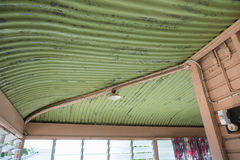 Old Queenslander house needing renovation, curved iron roof, foc. Traditional old curved iron roof on a house to be renovated, old electric wires Stock Photos
