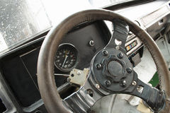 Old racecar steering wheel. Closeup of the steering wheel and dashboard of an antique racing car Royalty Free Stock Photo