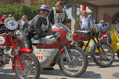 Old racing motorcycles. SAN PANCRAZIO, RAVENNA, ITALY - JUNE 2: Rob Nobels on Ducati 350 racing (1966) and Marilijna Jonker on Gilera 175 (1956) paused at fourth royalty free stock images