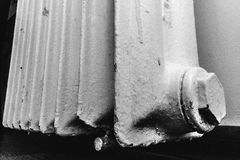 Old radiator. An old and damaged  cast-iron radiator Stock Image
