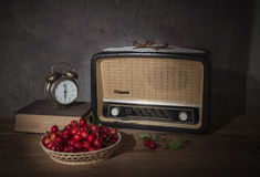 The old radio and fresh cherries Stock Photos