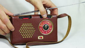 Old Radio Station Tuning. Tuning and search for radio stations on a portable old, vintage radio receiver in leather case stock video