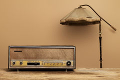 Old radio on wooden table with floor lamp Royalty Free Stock Photos