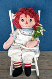 Old rag doll with daisies stock image