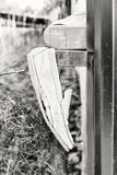 Old ragged shoes on fence. At summer day in black and white Royalty Free Stock Photos