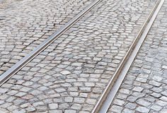 Old rail lines on cobbled road surface. Close Royalty Free Stock Photography