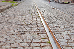Old rail lines on cobbled road surface. Close Stock Images
