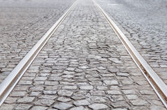 Old rail lines on cobbled road surface. Close Stock Photo