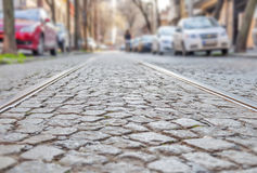 Old rail lines on cobbled road surface. Close Royalty Free Stock Photos