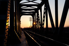 Railroad bridge in the warm sunset light. Old railroad bridge photographed at sunset Stock Photos