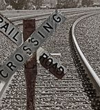 Old Railroad Crossing Sign. Railroad Crossing - Old Railroad Crossing Sign in front of a long curve of tracks in a rural area. Tinted image in dark, rich brown Stock Photography
