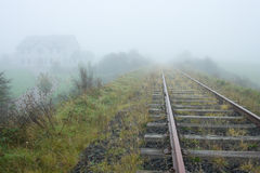 Old railroad and house vanishing in fog Stock Photo
