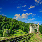 Old railroad passes in mountain village. Old railroad passes through the metal bridge in the mountain village Royalty Free Stock Image