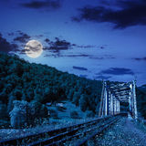 Old railroad passes in mountain village at night. Old railroad passes through the metal bridge in the mountain village at night in  full moon light Royalty Free Stock Photo