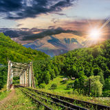 Old railroad passes in mountain village at sunset. Old railroad passes through the metal bridge in the mountain village at sunset Royalty Free Stock Photography