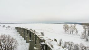 Old railway aqueduct, stone bridge. snow, winter time. aerial, copter shoot. Old abandoned historic railway bridge, snow, winter time. panorama, spans over the stock video footage