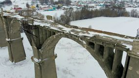 Old railway aqueduct, stone bridge. snow, winter time. aerial, copter shoot. Old abandoned historic railway bridge, snow, winter time. panorama, spans over the stock video
