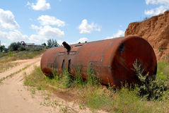 Old railway tank for transportation mineral oil. The old railway tank worth on the ground Royalty Free Stock Photo