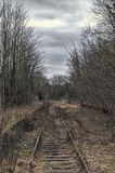 Old railway track surround by grass. And trees against a cloudy blue sky Stock Images