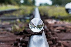 Old railway tracks with glass sphere on them and selective focus.  Stock Photos