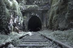 Old Railway Tunnel. A mysterious old railway tunnel is surrounded by lush greenery Royalty Free Stock Images