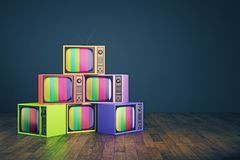 Old rainbow TV pile. Pile of old rainbow TVs in interior with blue wall and wooden floor. Creativity concept. 3D Rendering Royalty Free Stock Photography