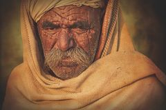 Old Rajasthani man against the background of his camels. Indian man attended the annual Pushkar Camel Mela Stock Image