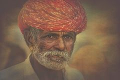 Old Rajasthani man against the background of his camels. Portrait indian man attended the annual Pushkar Camel Mela Royalty Free Stock Image