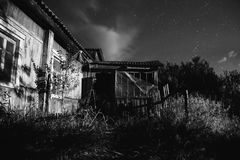 Black and white art monochrome photography. Old ramshackle house. The beautiful night scenery. Slow shutter speed. Spectacular clear starry sky. Scenic view Royalty Free Stock Images