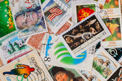 Old random used postage printed stamps from various countries and different time. For pattern, wallpaper, banner design. Old random used postage printed stamps Royalty Free Stock Photos