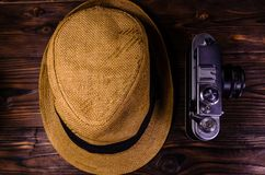 Old rangefinder camera and hat on a wooden table. Top view. Old rangefinder camera and hat on wooden table. Top view Stock Photos