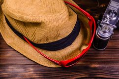 Old rangefinder camera, sunglasses and hat on a wooden table. Old rangefinder camera, sunglasses and hat on wooden table Royalty Free Stock Image