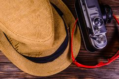 Old rangefinder camera, sunglasses and hat on a wooden table. To. Old rangefinder camera, sunglasses and hat on wooden table. Top view Royalty Free Stock Photography