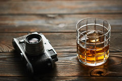 Old rangefinder camera and whiskey. Glass of whiskey and vintage old 35mm rangefinder camera on wooden background Royalty Free Stock Photo