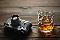 Old rangefinder camera and whiskey. Glass of whiskey and vintage old 35mm rangefinder camera on wooden background Stock Photos