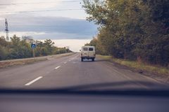 The old rarity van is on the road. View from the car.  Royalty Free Stock Photos