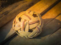 The old rattan ball (sepak takraw) on wood. The old rattan ball (sepak takraw) on wood Stock Photo