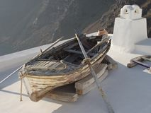 Old raw boat sits on the top of a white roof in Santorini. Greece Royalty Free Stock Images
