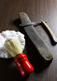 Old razor, sharpening leather and foam shaving brush on wooden b Stock Photography