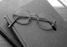 Old reading glasses and books. Pair of old and worn reading glasses on top of a couple books Stock Photos