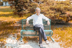 Old reassuring man resting on a bench Stock Photography