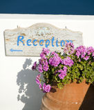 Old reception sign in the Greek Islands. Old painted fading hotel reception sign with typical flowers in Santorini Cyclades Greek Islands Greece Royalty Free Stock Photography