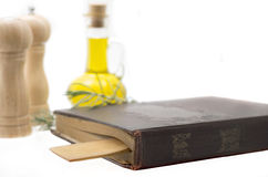 Old recipe-book. Olive oil, spices, recipe-book and wooden spoon on white backgroundk Stock Photo